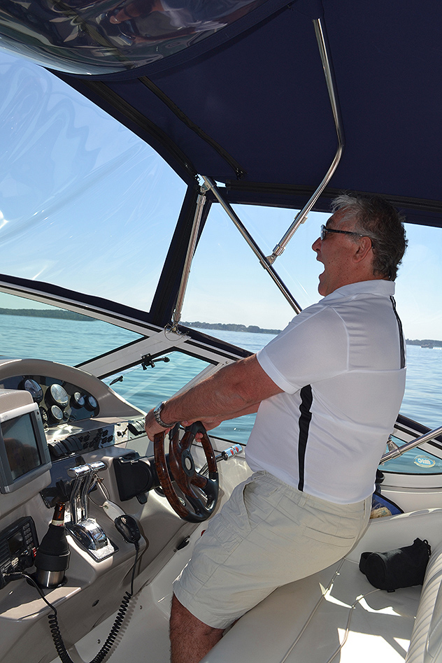 The boss at the helm headed south across a totally-flat Eastern Bay, 05JUL14